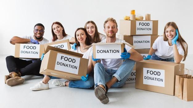 Voluntários sorridentes posando junto com caixas de doação de alimentos