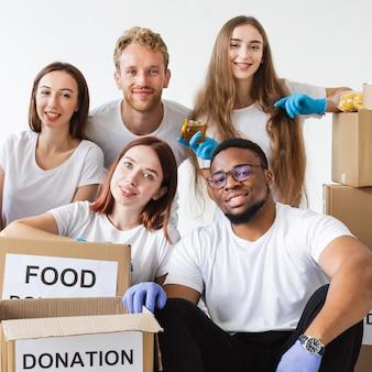 Voluntários sorridentes posando junto com doações de alimentos