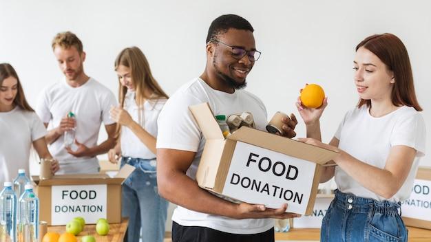 Voluntários sorridentes preparando caixa de comida para doação