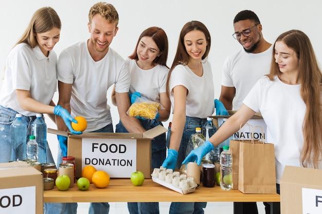 Voluntários sorridentes preparando caixas com alimentos para doação
