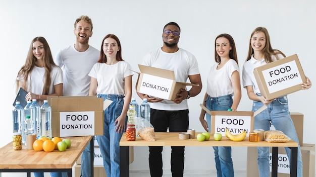 Voluntários sorridentes preparando caixas para doação com alimentos