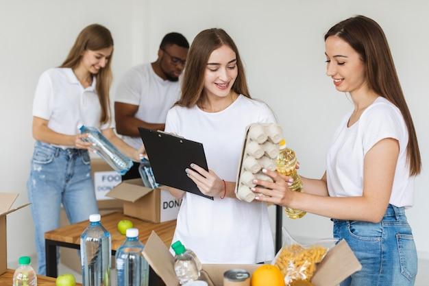 Voluntários sorridentes preparando comida para doação