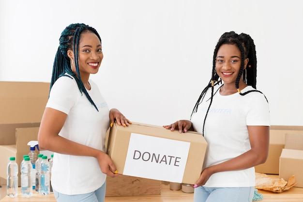 Voluntários sorridentes segurando uma caixa de doações