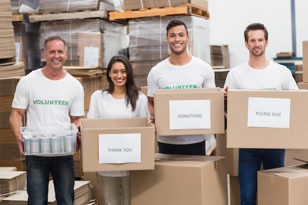 Voluntários sorrindo na câmera segurando caixas de doações