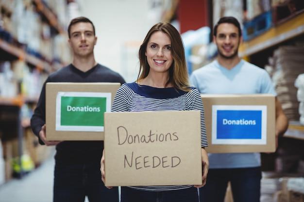 Voluntários sorrindo para a câmera segurando caixas de doações em um grande armazém