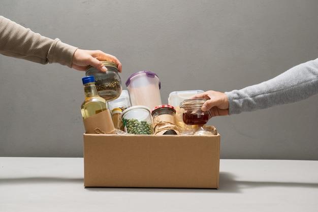 Voluntários tirando comida da caixa de doação na mesa