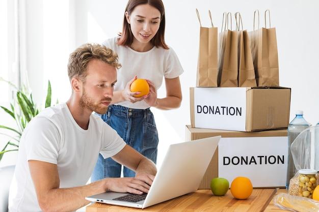Voluntários usando laptop para preparar caixas de doação de alimentos