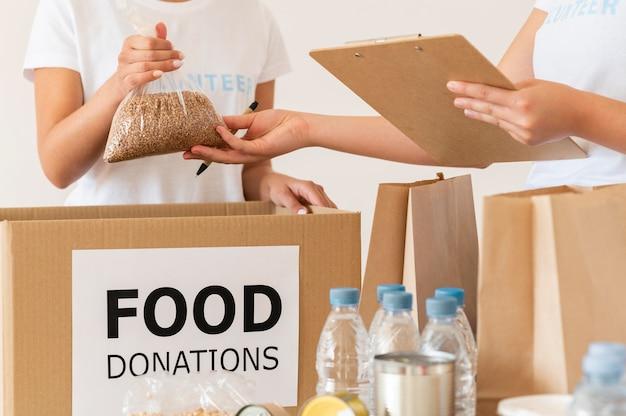 Voluntários verificando alimentos para doação com bloco de notas