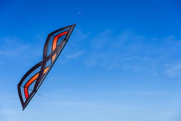 Voo acrobático do papagaio do conluio no céu azul.