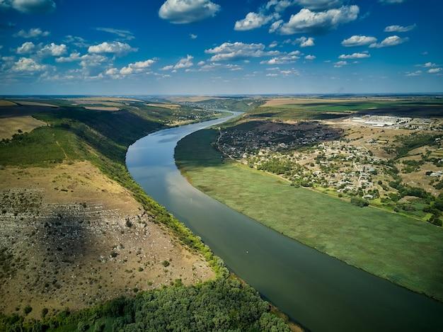 Voo através do majestoso rio dnister, exuberante floresta verde e vila. moldávia, europa.