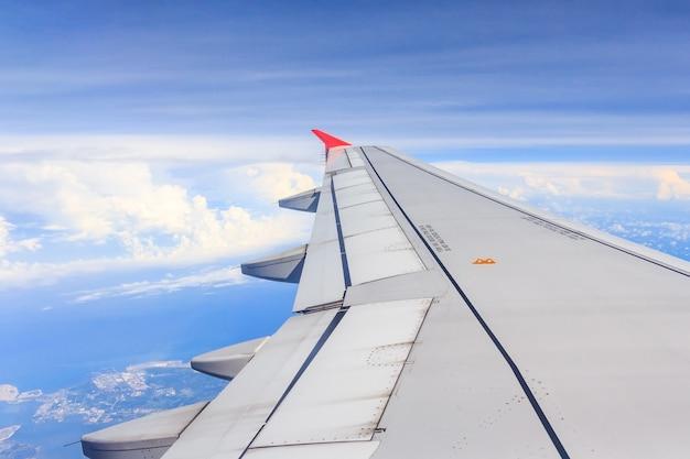 Voo da asa de aviões acima das nuvens no céu azul. das suas janelas