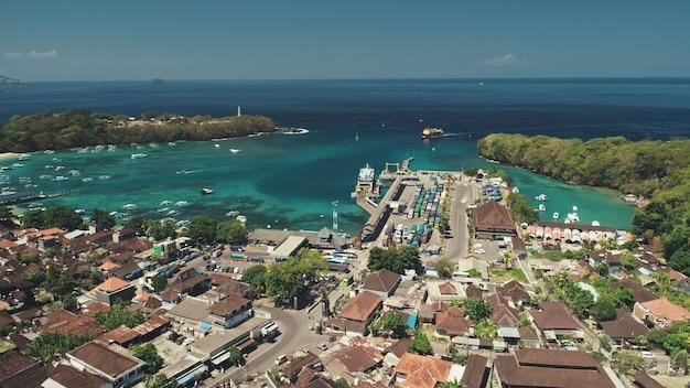 Voo de drone aéreo acima da floresta verde floresta telhado vermelho vila oceano baía porto porto e cais viagens
