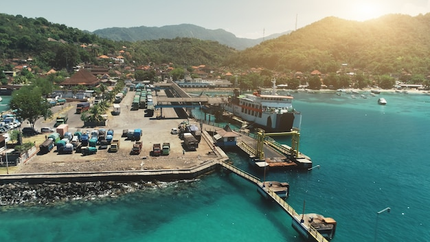 Voo de drone aéreo sobre caminhões do cais do porto do oceano, esperando na próxima balsa para outro paraíso