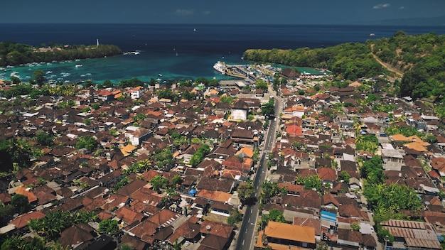 Voo de drone de vista aérea sobre a vila de telhado vermelho abriga a estrada de tráfego e a bela baía do porto oceânico