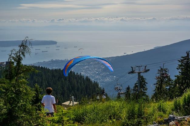 Voo de parapente com deslizamento azul e belas nuvens térmicas fofas no fundo. bela vista aérea