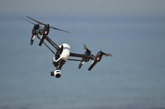 Voo de quadrocopter de uma câmera digital com gimbal de estabilização de 3 eixos sobre o mar