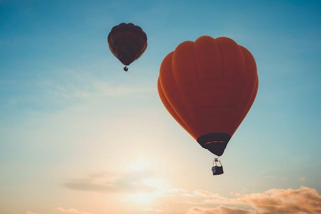 Vôo do balão de ar quente no céu no por do sol. conceito de viagens e transporte aéreo - estilo de efeito de filtro vintage e retrô