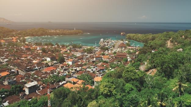 Voo do drone sobre a vila da selva, a baía do oceano abriga o cais do porto no turismo de viagem luz do sol