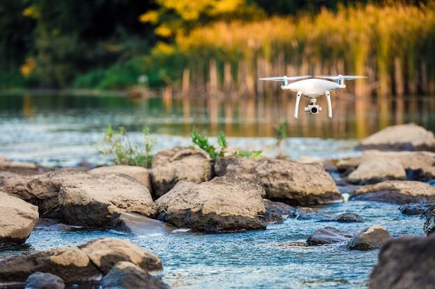 Voo do zangão de quadcopter com uma câmera sobre um lago.