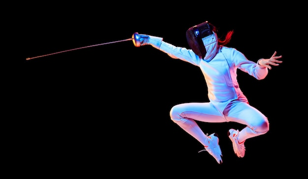 Vôo. menina adolescente em traje de esgrima com espada na mão, isolada na parede preta, luz de néon. jovem modelo praticando e treinando em movimento, ação. copyspace. esporte, estilo de vida saudável. folheto.