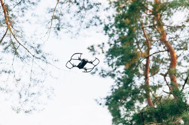 Voo pequeno do quadrocopter do zangão esperto no céu branco e em árvores verdes.