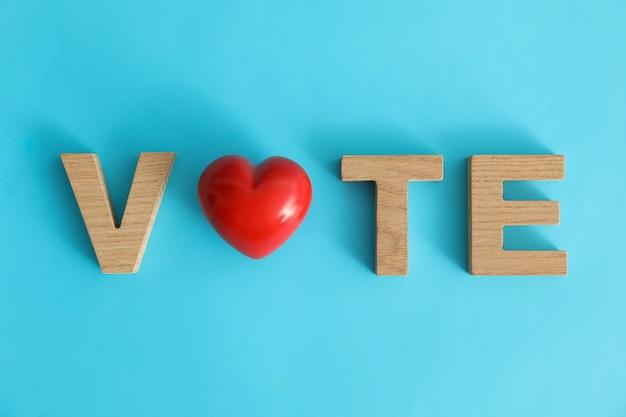 Voto de palavra feito de letras de madeira e coração na superfície azul