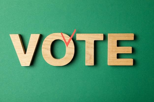 Voto de palavra feito de letras de madeira na superfície verde