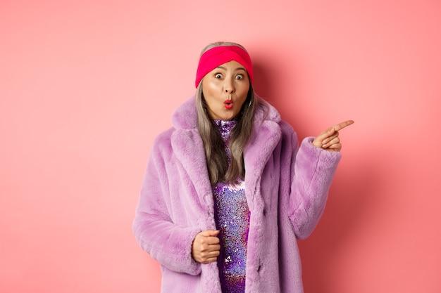 Vovó asiática legal apontando o dedo para a direita e mostrando a oferta promocional, verificando ofertas especiais no fundo rosa