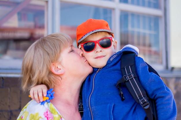 Vovó beija seu neto. rapaz vestido na moda com a avó