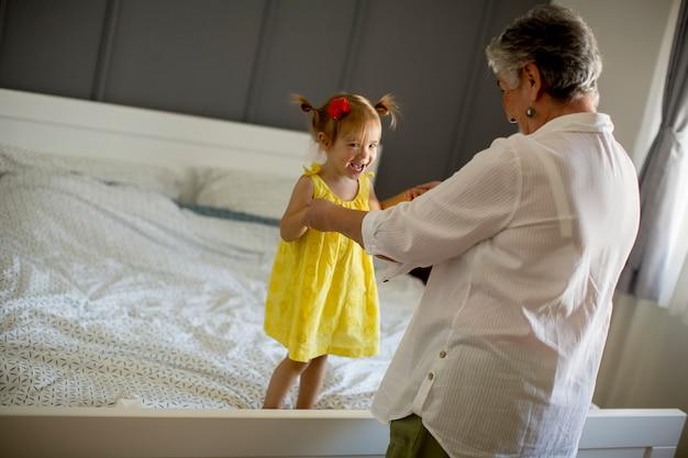 Vovó brinca com uma netinha na cama