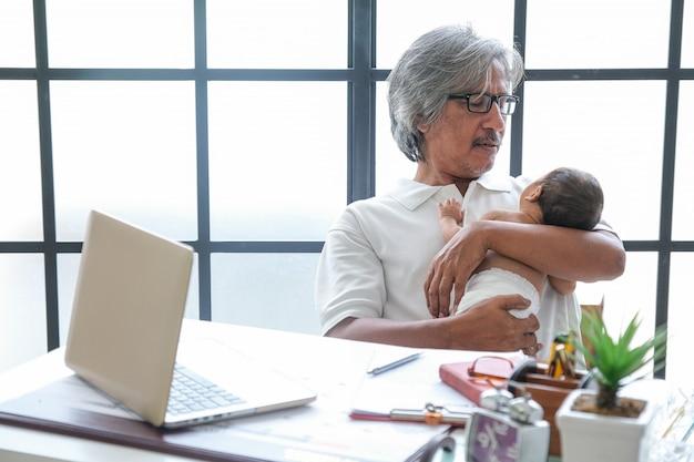 Vovô carregando neto enquanto trabalhava em uma mesa com um laptop e equipamento de escritório