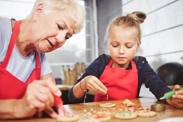 Vovó com garota aplicando cobertura em biscoitos