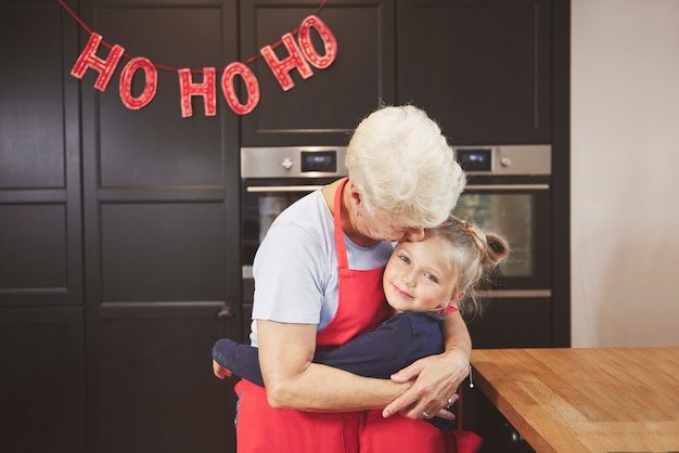Vovó com neta se abraçando na cozinha
