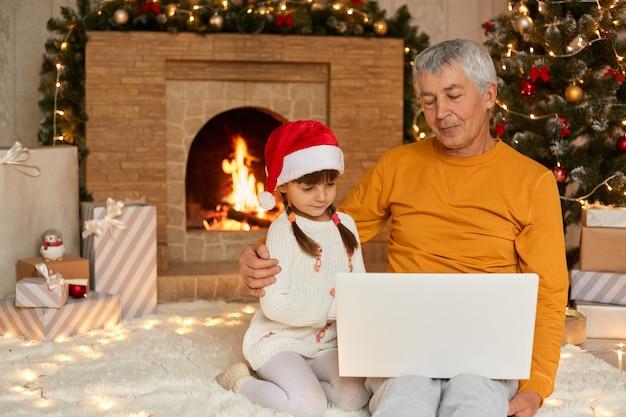 Vovô com seu neto sentado no chão e olhando para a tela do notebook, garoto com chapéu de papai noel parece tímido, família tendo videochamada, posando na sala com lareira e decorações de ano novo.
