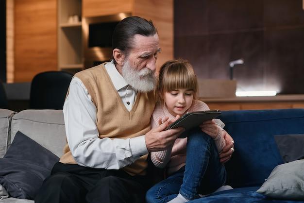 Vovô com sua neta usando o tablet pc em casa aconchegante. menina ensina seu avô a usar dispositivos inteligentes.