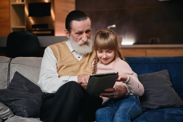 Vovô com sua neta usando tablet em casa aconchegante.