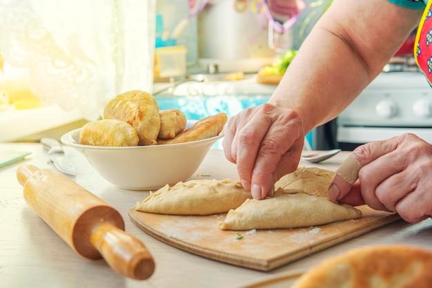 Vovó cozinha tortas. comida caseira. bolos de massa feitos à mão nas mãos das mulheres. o processo de fazer massa de torta manualmente