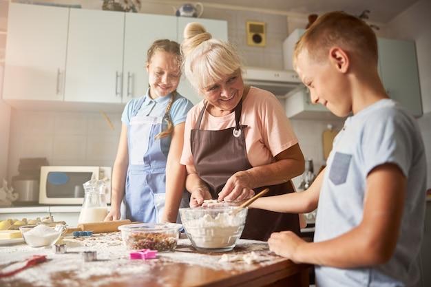 Vovó de bom coração fazendo biscoitos com seus netos fofos