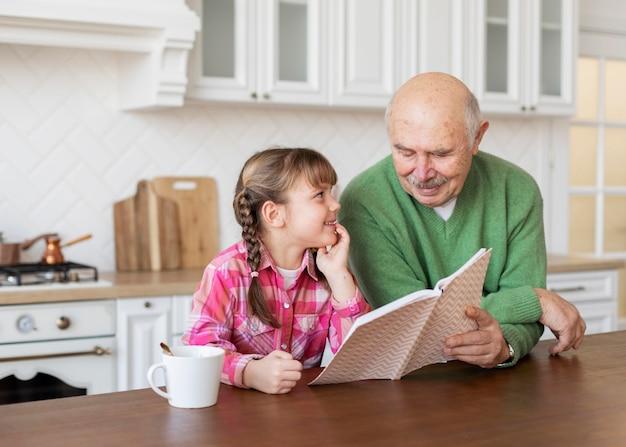 Vovô de tiro médio e menina com livro