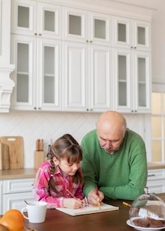 Vovô de tiro médio e menina na cozinha