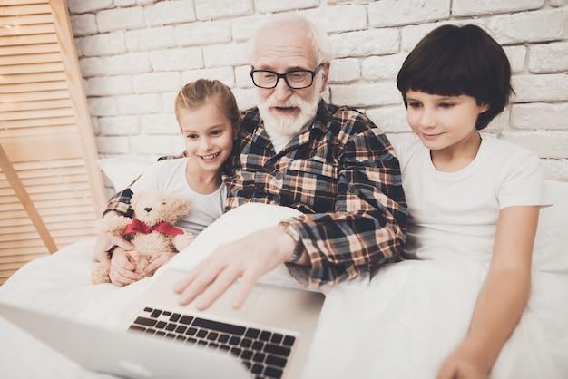 Vovô e crianças assistem filmes na cama lazer em casa