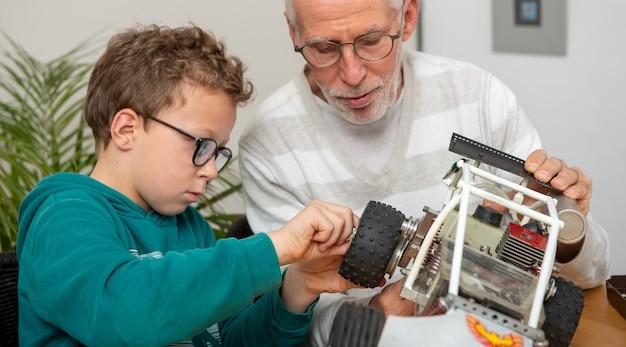 Vovô e filho, garotinho, consertando um modelo de carro controlado por rádio