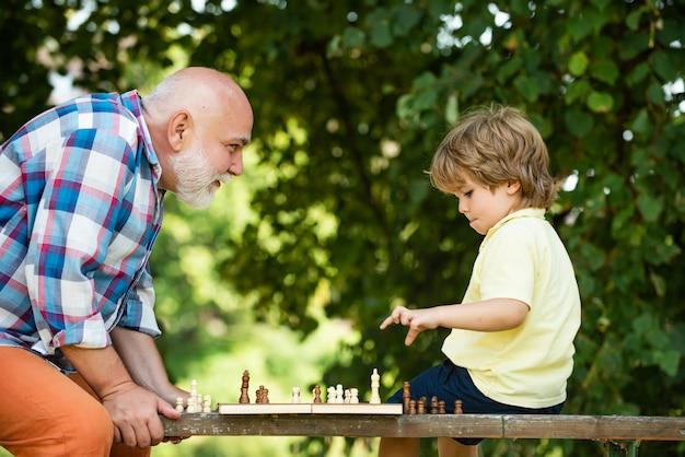 Vovô e neto bonitos estão jogando xadrez enquanto passam o tempo juntos, garotinho jogando ches ...