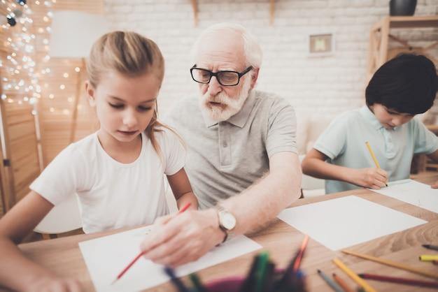 Vovô ensina as crianças a desenhar o tempo feliz juntos.