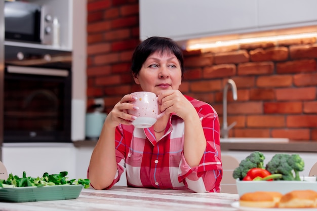 Vovó está sentada à mesa na cozinha, tomando café e descansando