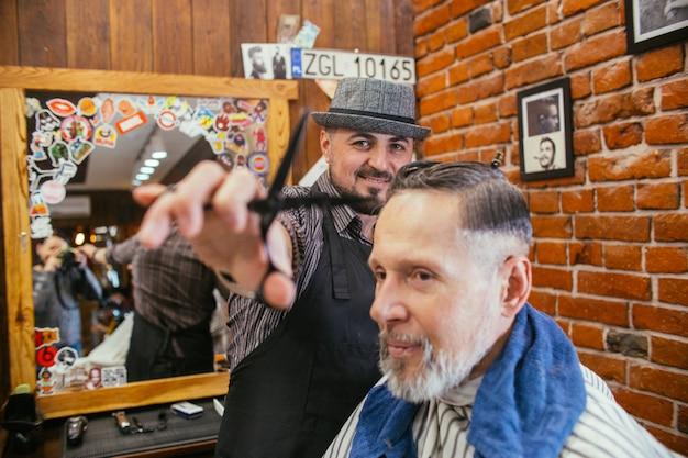 Vovô faz um corte de cabelo no cabeleireiro barber shop.