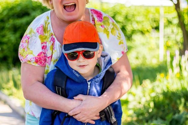 Vovó feliz abraçou o neto e rindo divertida, regozijando-se em se comunicar com o menino