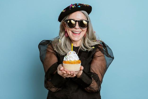 Vovó legal comemorando seu aniversário com um cupcake