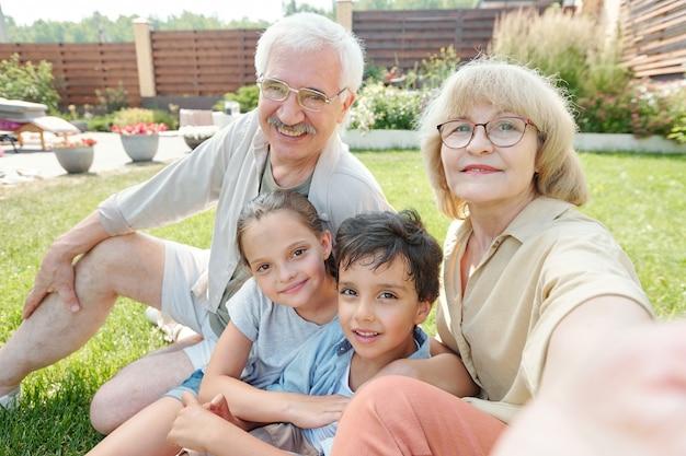 Vovó moderna tirando fotos de si mesma, do marido e dos netos na câmera do smartphone