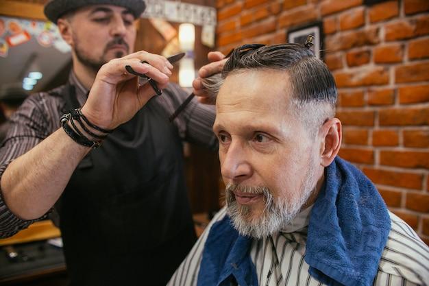 Vovô recebe um cabeleireiro de corte de cabelo na barbearia